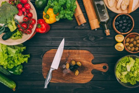 Photo for Top view of chopping board with olivesr and knife on table with vegetables - Royalty Free Image