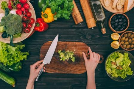 Photo for Top view of cropped hands slicing broccoli on table with vegetables - Royalty Free Image