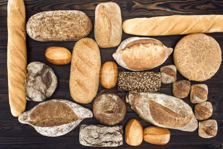 Photo for Top view of various organic homemade bread loaves on wooden table - Royalty Free Image