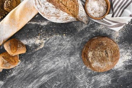 Photo for Top view of assortment of healthy homemade bread and flour on black - Royalty Free Image