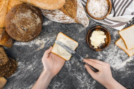 person spreading butter on toast