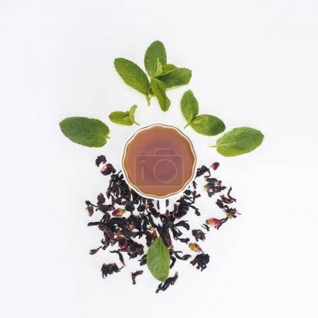 Photo for Top view of healthy herbal tea in cup and mint leaves on grey - Royalty Free Image
