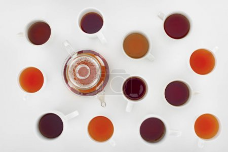 Photo for Top view of assorted herbal tea in cups and teapot on grey - Royalty Free Image