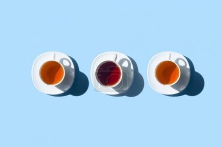 Photo pour Vue de dessus de trois tasses avec tisane fraîche isolée sur bleu - image libre de droit