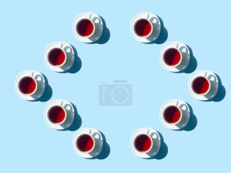 Photo for Top view of frame made from healthy herbal tea in cups with shadows on blue - Royalty Free Image
