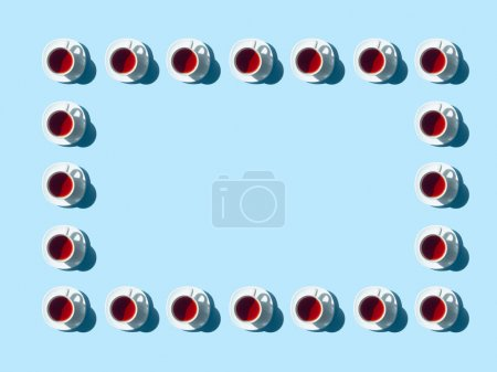 Photo for Top view of frame made from tea cups and saucers with shadows on blue - Royalty Free Image