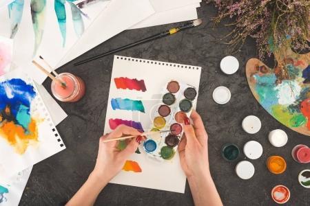 artist mixing watercolor paints