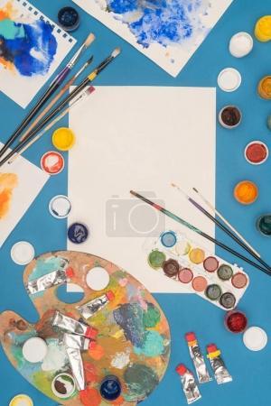 Foto de Vista superior de la hoja vacía de papel y diferentes pinturas sobre una mesa turquesa - Imagen libre de derechos