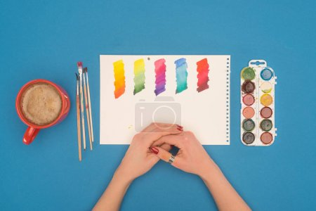 Photo for Cropped image of designer looking at diluted paints - Royalty Free Image