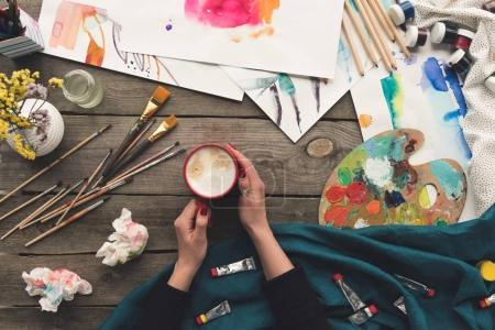 Photo pour Image recadrée du peintre buvant du café sur le lieu de travail - image libre de droit