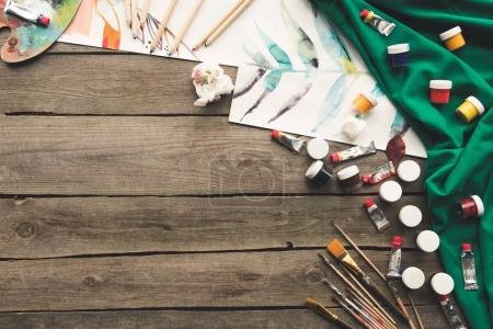 Photo for Top view of scattered different paint and sketches on an artist table - Royalty Free Image