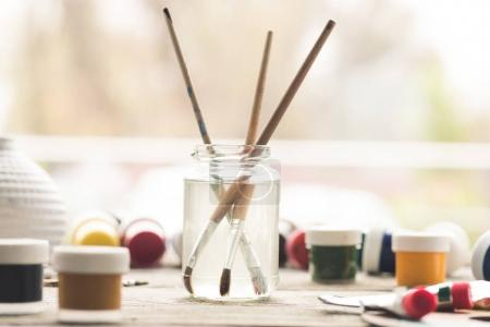 Photo for Paint brushes in a solvent and scattered containers with poster paints - Royalty Free Image