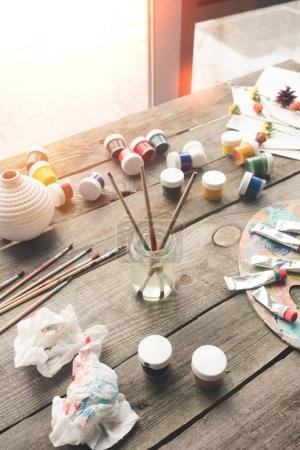 Photo for Paint brushes in a water and scattered containers with poster paints - Royalty Free Image