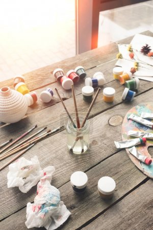 Paint brushes and scattered paints