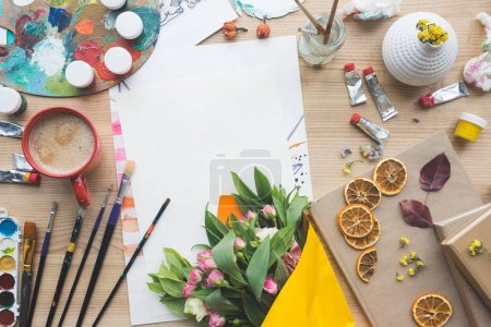 Photo for Top view of empty sheet of paper and flowers on a painter table - Royalty Free Image