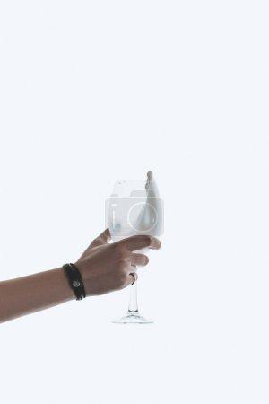 Photo pour Vue recadrée de main tenant le verre avec du lait, isolé sur blanc - image libre de droit