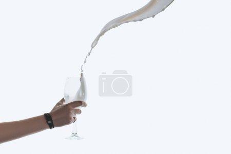 Photo pour Vue recadrée de main tenant le verre avec soupçon de lait, isolé sur blanc - image libre de droit