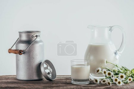 Photo for Jugs and glass of fresh milk with chamomile flowers on shabby wooden tabletop - Royalty Free Image
