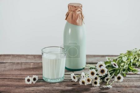 Photo pour Bouteille et verre de lait frais avec les fleurs de camomille sur table en bois - image libre de droit