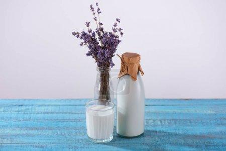 Photo pour Bouteille et verre de lait frais à la lavande dans un vase sur une table en bois bleue - image libre de droit