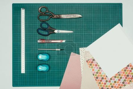 Top view of sheets of paper and scissors with stationery knife for making scrapbooking postcard