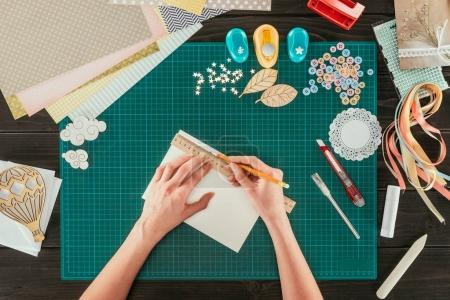 cropped image of woman measuring paper for scrapbooking postcard