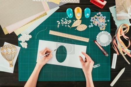 cropped image of designer making scrapbooking decoration for postcard
