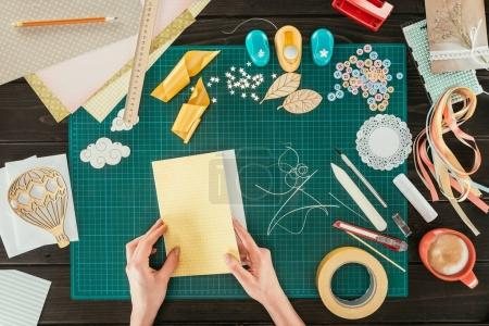 cropped image of designer making template for scrapbooking postcard
