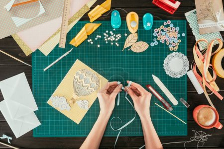 Photo for Cropped image of designer making bow with ribbon - Royalty Free Image