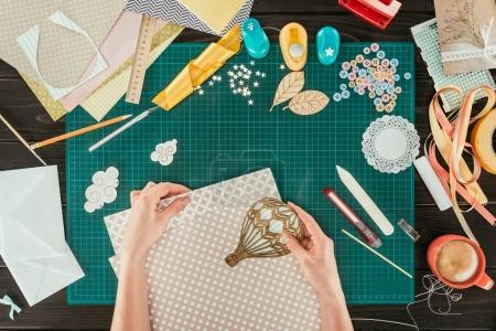 Photo for Cropped image of woman putting wooden balloon on sheet of paper - Royalty Free Image