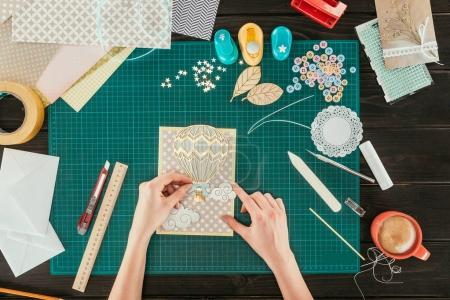 cropped image of woman adding decorative clouds on scrapbooking handmade postcard
