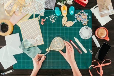cropped image of woman putting sequins on scrapbooking balloon
