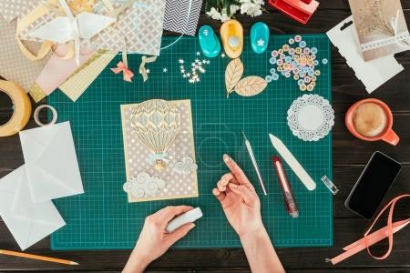 cropped image of woman decorating scrapbooking postcard with star