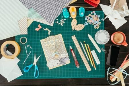 Top view of designer working place with scrapbooking postcard template