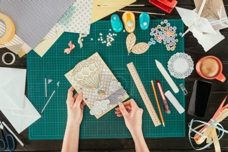 cropped image of artist holding scrapbooking handmade postcard with wooden balloon