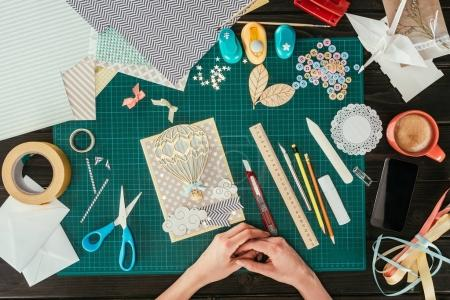 cropped image of designer sitting with scrapbooking handmade postcard at working table