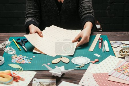 cropped image of designer choosing paper for scrapbooking postcard