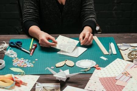 Photo pour Image recadrée du designer assis à table et faisant scrapbooking carte postale - image libre de droit