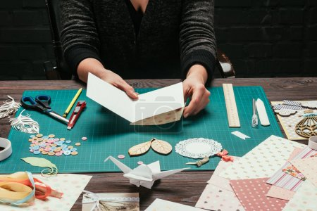 cropped image of designer making cover for scrapbooking handmade postcard