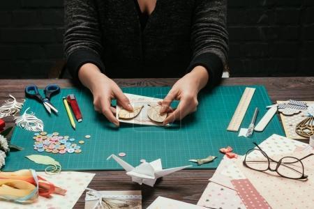 Photo pour Image recadrée du concepteur ajoutant des feuilles de bois à la couverture de carte postale scrapbooking - image libre de droit