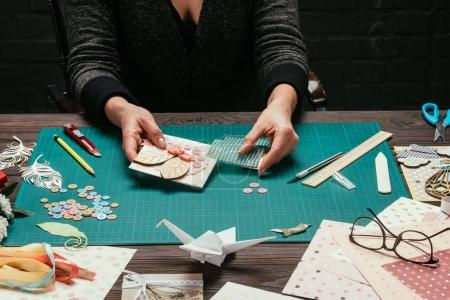 cropped image of woman adding sequins to scrapbooking postcard