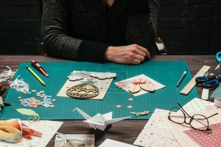 cropped image of scrapbooking designer sitting at working table