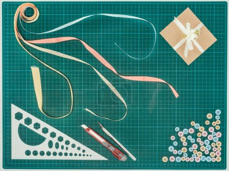 Top view of scrapbooking postcard with ruler and buttons on turquoise scale