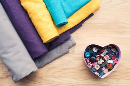 top view of wooden table with rolls of fabric and heart shaped box with buttons