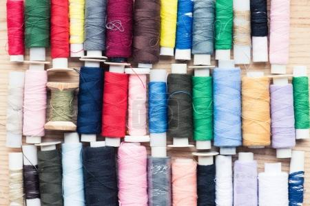colorful stitchings over wooden background