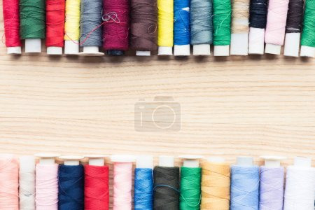 colorful frame of stitchings over wooden background with copy space