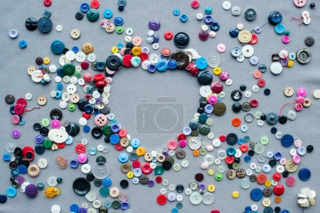 top view of colorful buttons heart shaped frame on grey cloth background