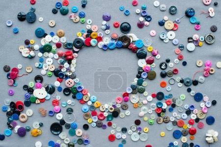 Photo pour Vue de dessus des boutons colorés cadre en forme de coeur sur fond de tissu gris - image libre de droit