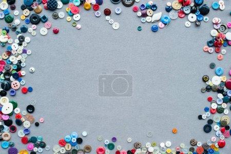 Photo pour Vue de dessus du cadre de boutons colorés sur fond de tissu gris - image libre de droit