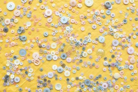 Photo pour Vue de dessus des touches colorées éparpillées sur fond de tissu jaune - image libre de droit